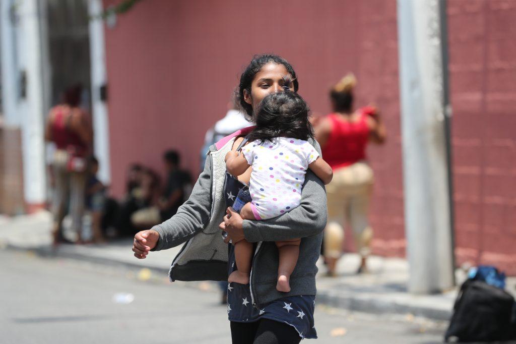 Una mujer viaja con su hija en brazos.