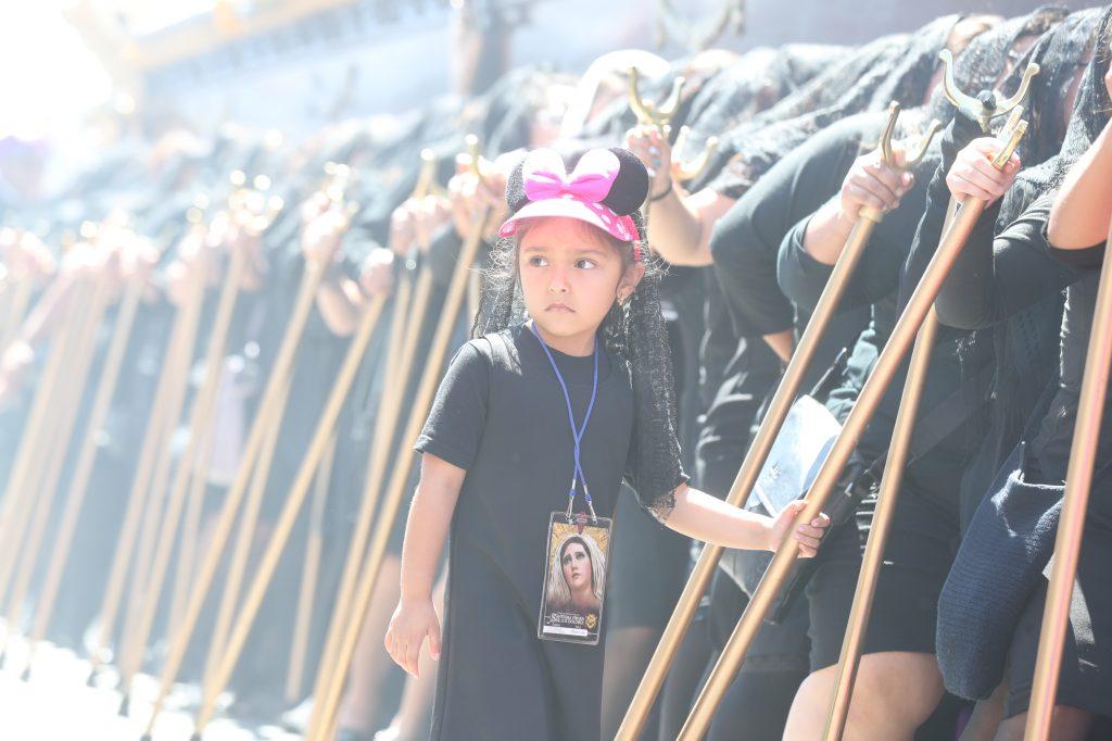 Una niña porta un gorro de una figura animada mientras acompaña a su madre en la procesión.