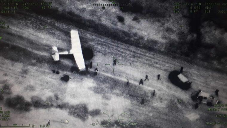 Esta fotografía fue captada desde una aeronave del Ejército y se evidencia cuando varias personas sacan cargamentos de la avioneta en el Manchón Guamuchal, Retalhuleu. (Foto Prensa Libre: Cortesía)