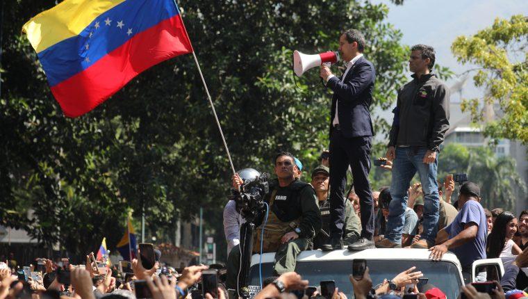 El presidente de la Asamblea Nacional, Juan Guaidó  y el líder opositor Leopoldo López participan en una manifestación en apoyo a su levantamiento. (Foto Prensa Libre: EFE)