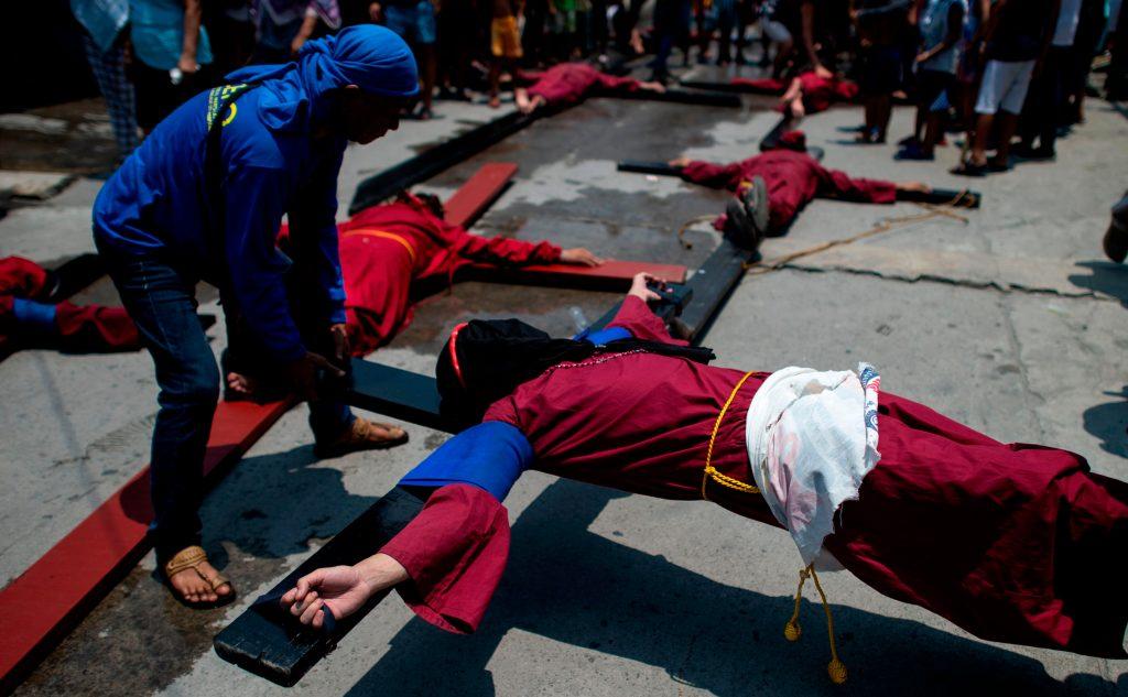 Devotos cristianos cubren sus rostros mientras esperan en sus cruces durante un acto de crucifixión en Filipinas. Foto Prensa Libre: AFP