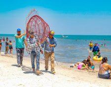 Personal de la comuna traslada una estructura metálica en forma de pez para instalarla como recolector de desechos de plástico en la playa Punta de Palma, Puerto Barrios, Izabal. (Foto Prensa Libre: Dony Stewart)