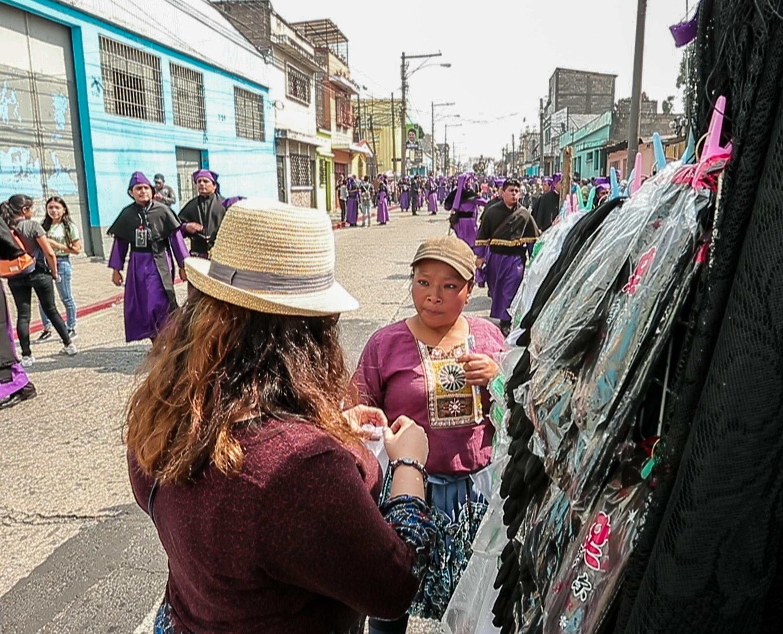 Carmen Pérez -con gorra- ofrece sus productos durante la procesión de Jesús de las Tres Potencias del Lunes Santo. (Foto Prensa Libre: Juan Diego González).