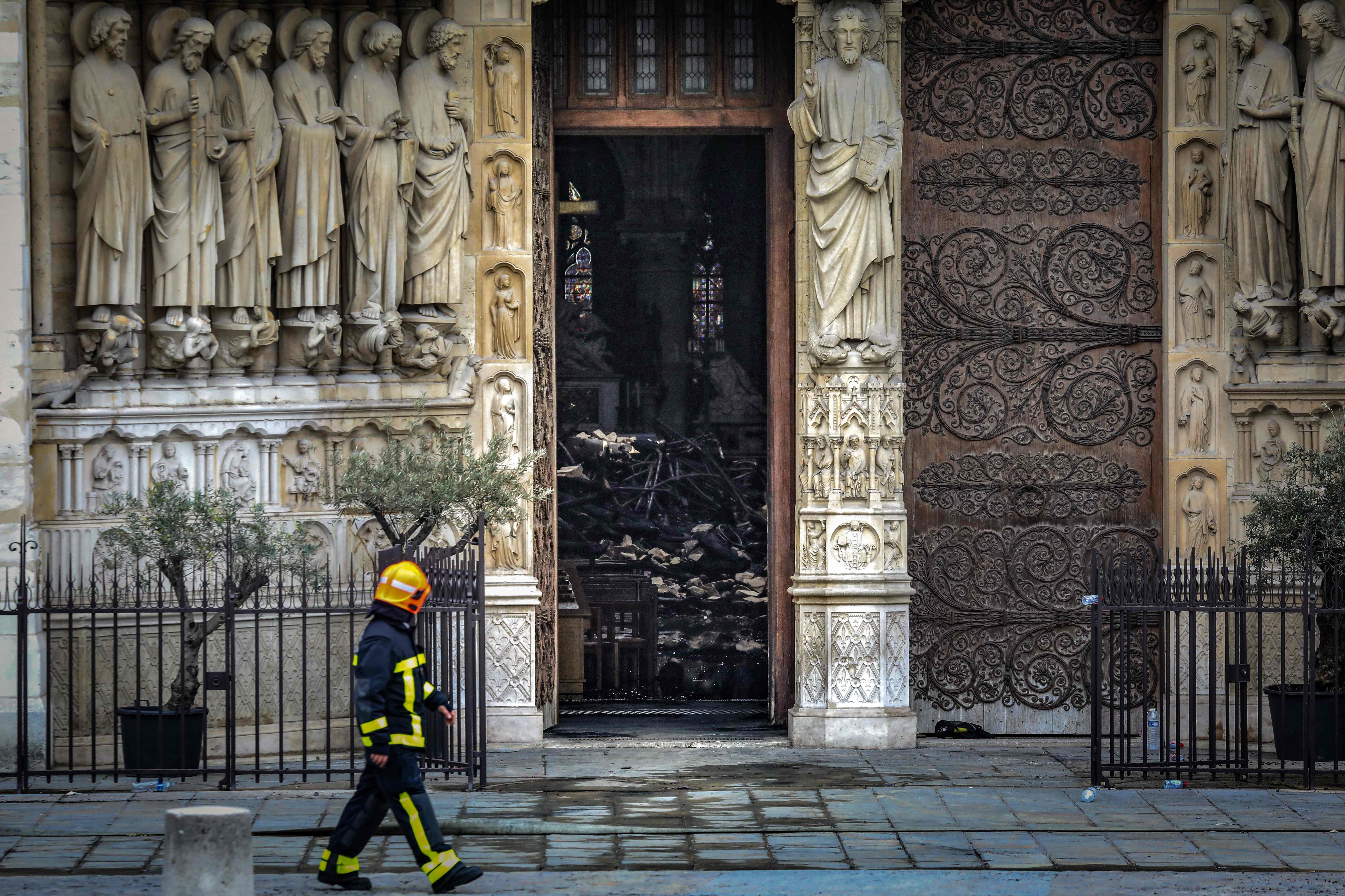 Bomberos evalúan el lugar después de que se desplomara el techo y la torre de la Catedral. Foto Prensa Libre: AFP