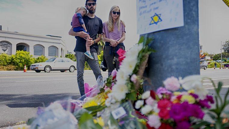 Una familia observa un memorial improvisado al otro lado de la calle de la Sinagoga Chabad de Poway, California, un día después de que un hombre armado disparara y matara a una e hiriera a tres. (Foto Prensa Libre: AFP).