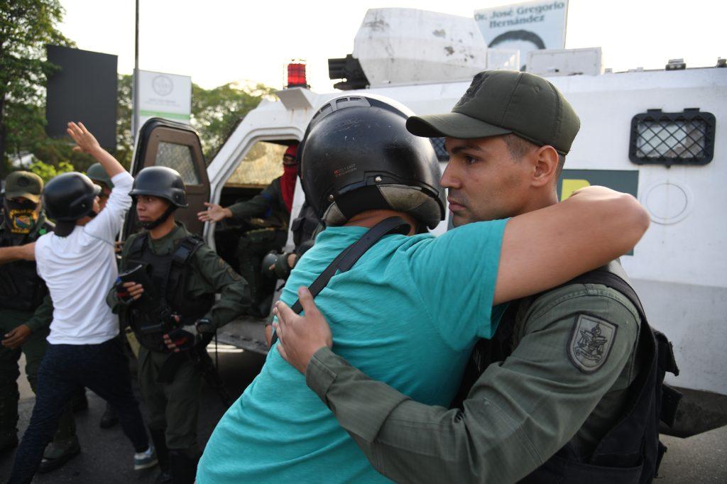 Un hombre venezolano abraza a un miembro de las fuerzas de seguridad  como símbolo de paz. Foto Prensa Libre: AFP