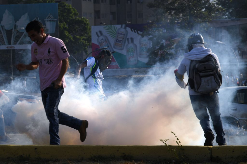 Los venezolanos huyen de gas lacrimógeno durante las peleas con las fuerzas de seguridad en Caracas la mañana del 30 de abril. Foto Prensa Libre: AFP