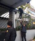 Un policía trepa en uno de los inmuebles en donde este viernes se llevó a cabo uno de los allanamientos en busca de los integrantes de al red de lavado. (Foto: PNC)