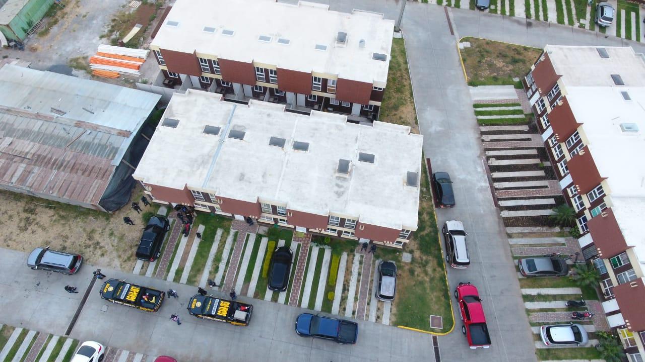 Agentes de la PNC resguardan viviendas donde se efectúan los operativos contra traficantes de personas. (Foto Prensa Libre: PNC)