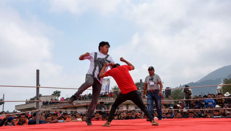 Competitors fight during a traditional bare knuckle boxing tournament at the Chivarreto village, Totonicapan departament, 205 km west of Guatemala city on April 19, 2019. - Improvised fighters box with a clean fist in a centennial tradition to commemorate Good Friday and the crucifixion of Jesus. (Photo by Johan ORDONEZ / AFP)