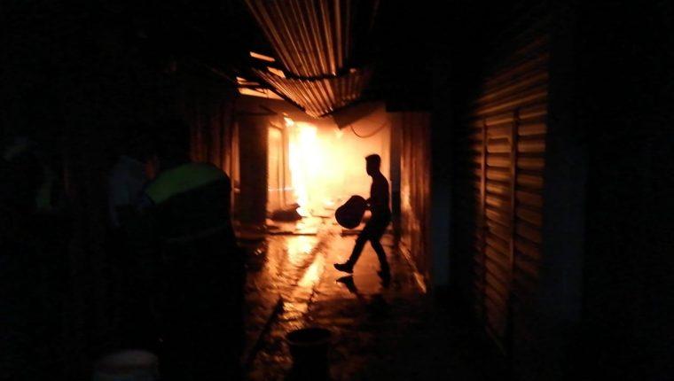 Vendedores intentan sofocar las llamas que destruye varios comercios en el mercado La Económica. (Foto Prensa Libre: Cortesía)