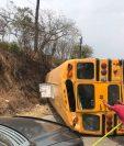Pilotos y vecinos movilizan el autobús accidentado para liberar el paso en la ruta a San Raymundo. (Foto: Bomberos Municipales de Mixco)