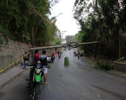 Vecinos de unas 10 colonias de la zona 18 quedaron aisladas por la caída de un poste de energía eléctrica en la carretera. (Foto Prensa Libre: La Red)