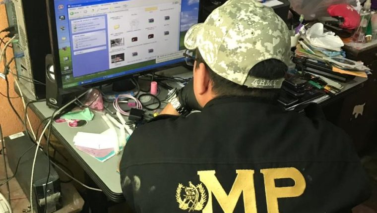 Un fiscal del Ministerio Público revisa la computadora de David Alejandro Pascual Argueta, alias Valdroxx, quien es señalado de producir y vender pornografía infantil. (Foto Prensa Libre: Cortesía)