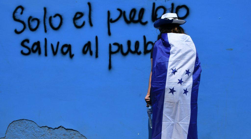 Un manifestante permanece al lado de un graffiti durante una manifestación en Tegucigalpa. Foto Prensa Libre: AFP