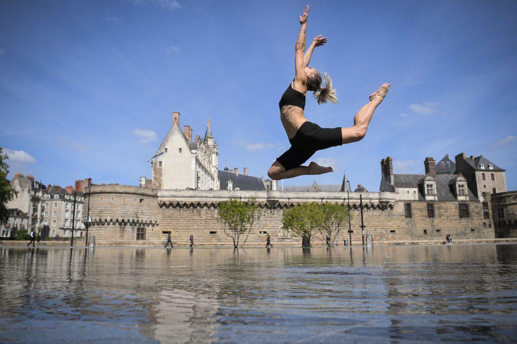 Una mujer baila en el Miroir d'Eau (Espejo de agua) frente al castillo de los Duques de Bretaña en Dantes, Francia. Foto Prensa Libre: AFP