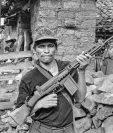 Un miliciano rebelde alza su rifle en un gesto de desafío frente a su casa en el departamento de Chalatenango, ocupado por los rebeldes. El Salvador, 1984. Foto por Scott Wallace.