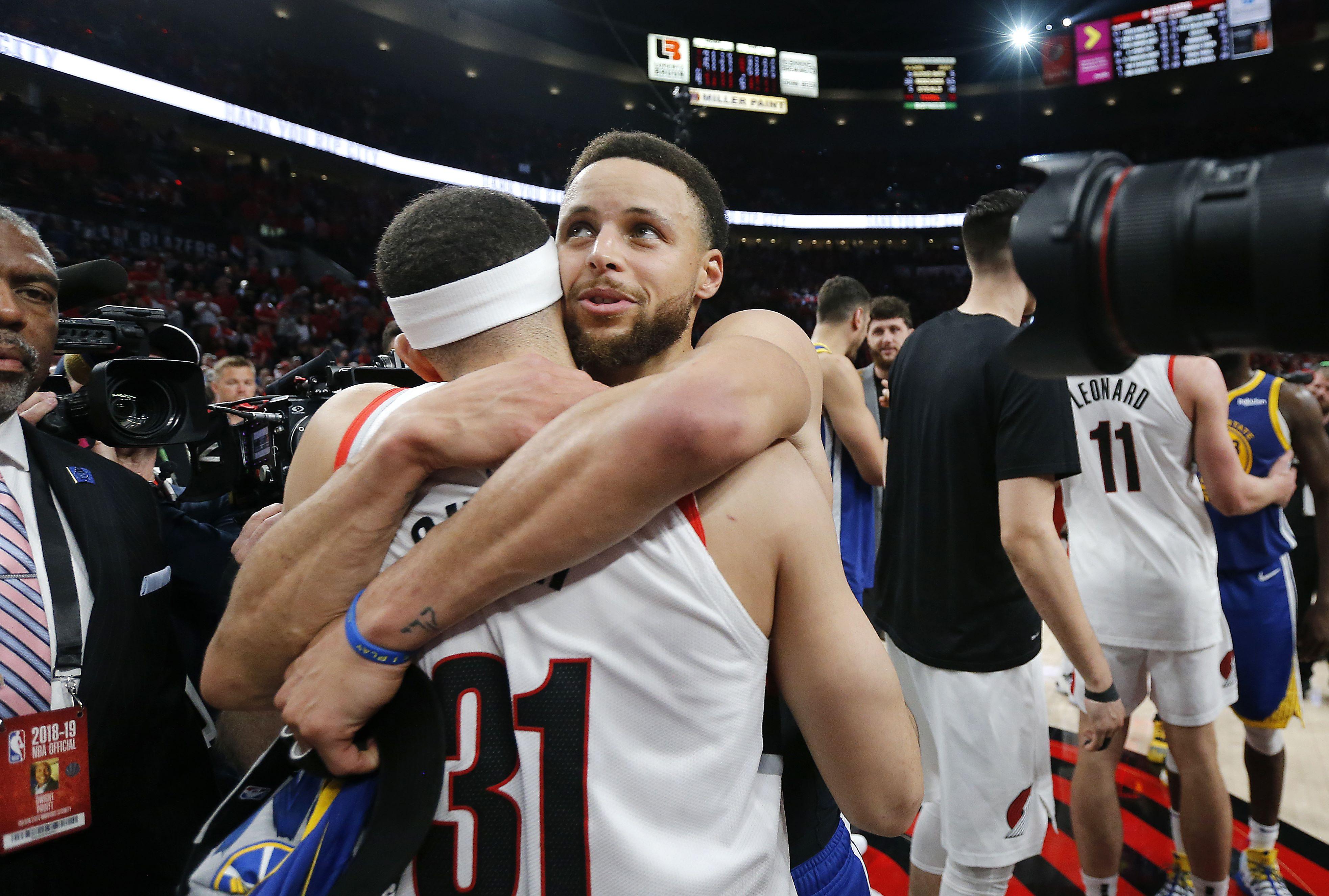 Stephen Curry abraza a su hermano Seth, de los Portland Trail Blazers, durante el último partido de la final de la Conferencia Oeste. (Foto Prensa Libre: AFP) == FOR NEWSPAPERS, INTERNET, TELCOS & TELEVISION USE ONLY ==