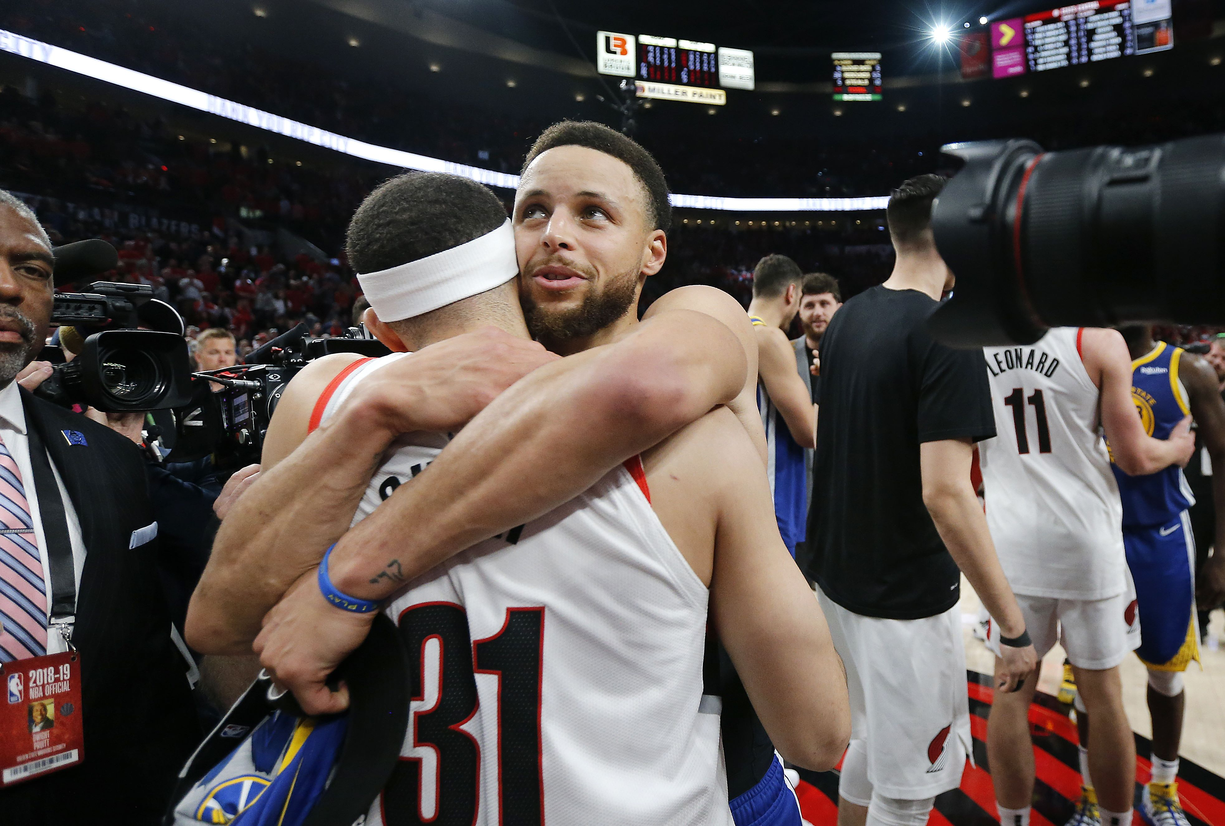Stephen Curry abraza a su hermano Seth, de los Portland Trail Blazers, durante el último partido de la final de la Conferencia Oeste. (Foto Prensa Libre: AFP)
