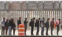 EL PASO, NM - MAY 17: Migrants stand while being detained by Border Patrol, after crossing to the U.S. side of the U.S.-Mexico border barrier (background), on May 17, 2019 in El Paso, Texas. The location is an area where migrants frequently turn themselves and ask for asylum after crossing the border. Approximately 1,000 migrants per day are being released by authorities in the El Paso sector of the U.S.-Mexico border amidst a surge in asylum seekers arriving at the Southern border.   Mario Tama/Getty Images/AFP == FOR NEWSPAPERS, INTERNET, TELCOS & TELEVISION USE ONLY ==