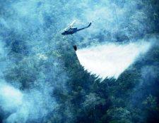 Un helicóptero apoya las labores para combatir los incendios forestales activos en Petén. (Foto Prensa Libre: Conred).