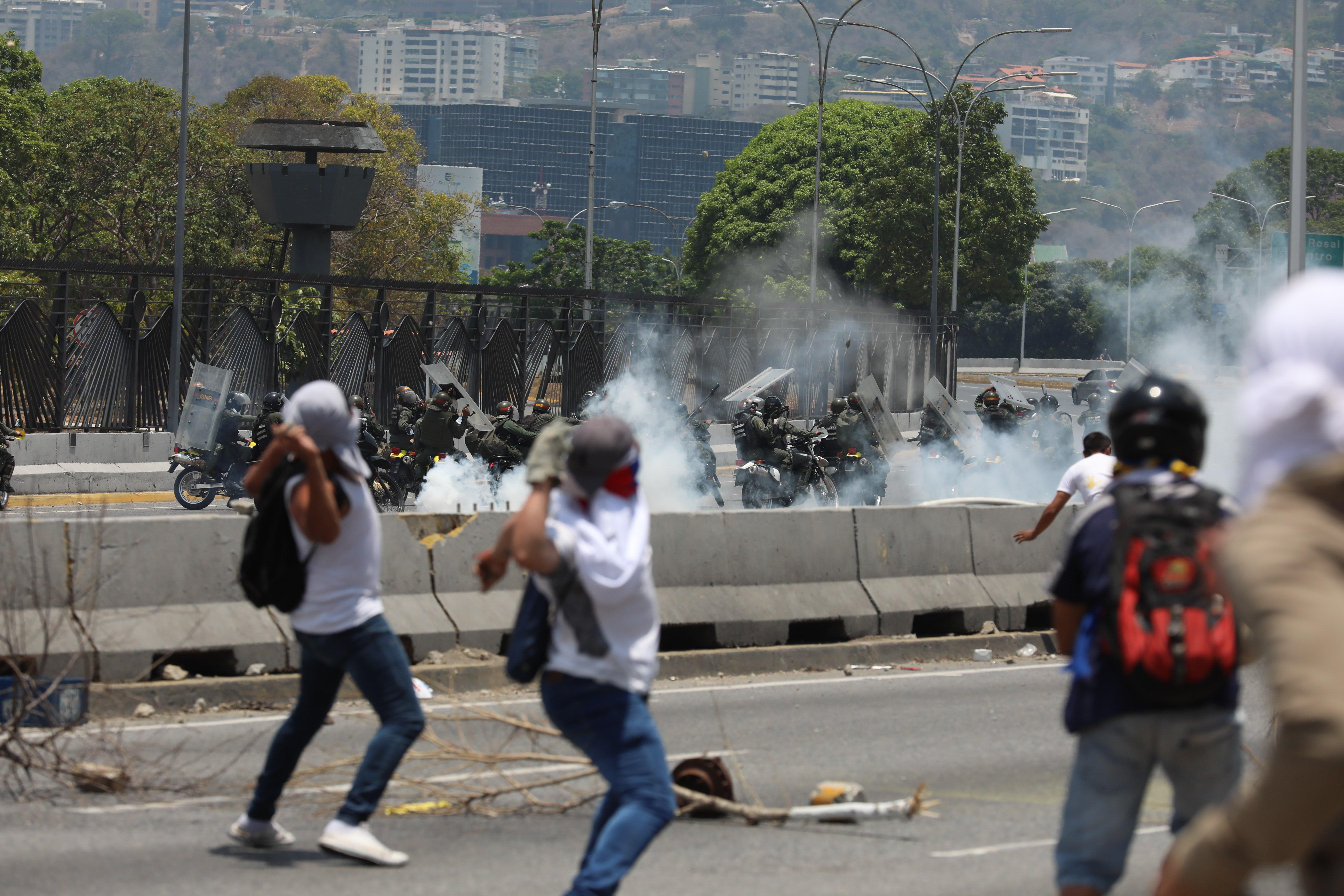 Manifestantes opositores se enfrentan con miembros de la Guardia Nacional Bolivariana en las calles de Caracas. (Foto Prensa Libre: EFE)
