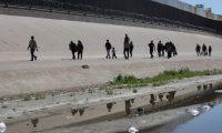 """MEX1644. PASO DEL NORTE (MÉXICO), 09/05/2019.-Unos 500 migrantes centroamericanos caminan este jueves sobre el río Bravo, en Ciudad Juárez, en el estado de Chihuahua (México), para cruzar la línea fronteriza hacia Estados Unidos y entregarse a la policía migratoria norteamericana. El presidente de México, Andrés Manuel López Obrador, defendió este jueves la protección a los migrantes que llegan a México en busca de un futuro mejor, declaraciones que contrastan con los 43.301 deportados que suma su corto mandato. En conferencia de prensa, el líder izquierdista, que tomó posesión del cargo en diciembre de 2018, insistió en su propósito de que """"los que llegan al sur (del país) tengan visa de trabajo en México y se les den opciones"""".EFE/ David Peinado"""