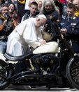 El papa Francisco firma en el depósito de una Harley Davidson mientras saluda a miembros de la asociación de motociclistas. (Foto Prensa Libre: EFE)