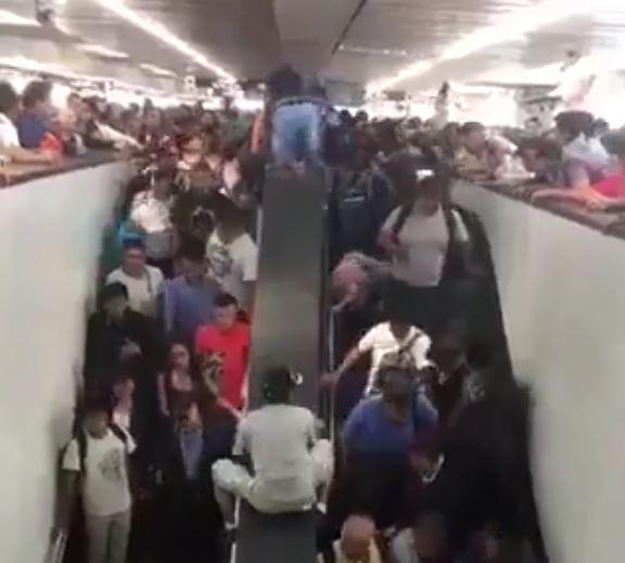 Espantados, los usuarios del metro quedan atrapados entre las gradas eléctricas y el gentío en una estación del metro.