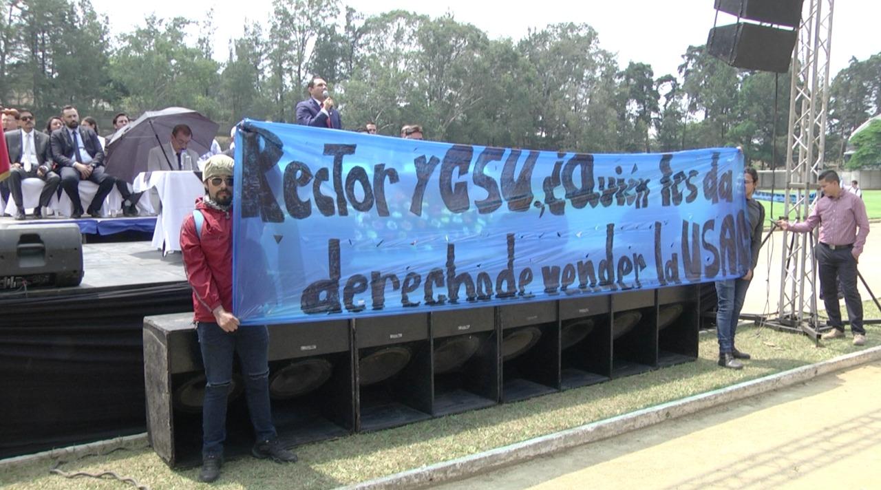 Sancarlistas mostraron una manta contra el rector Murphy Paiz y el Consejo Superior durante el acto de juramentación d ela misión de observación electoral.  (Foto Prensa Libre: Dulce Rivera)