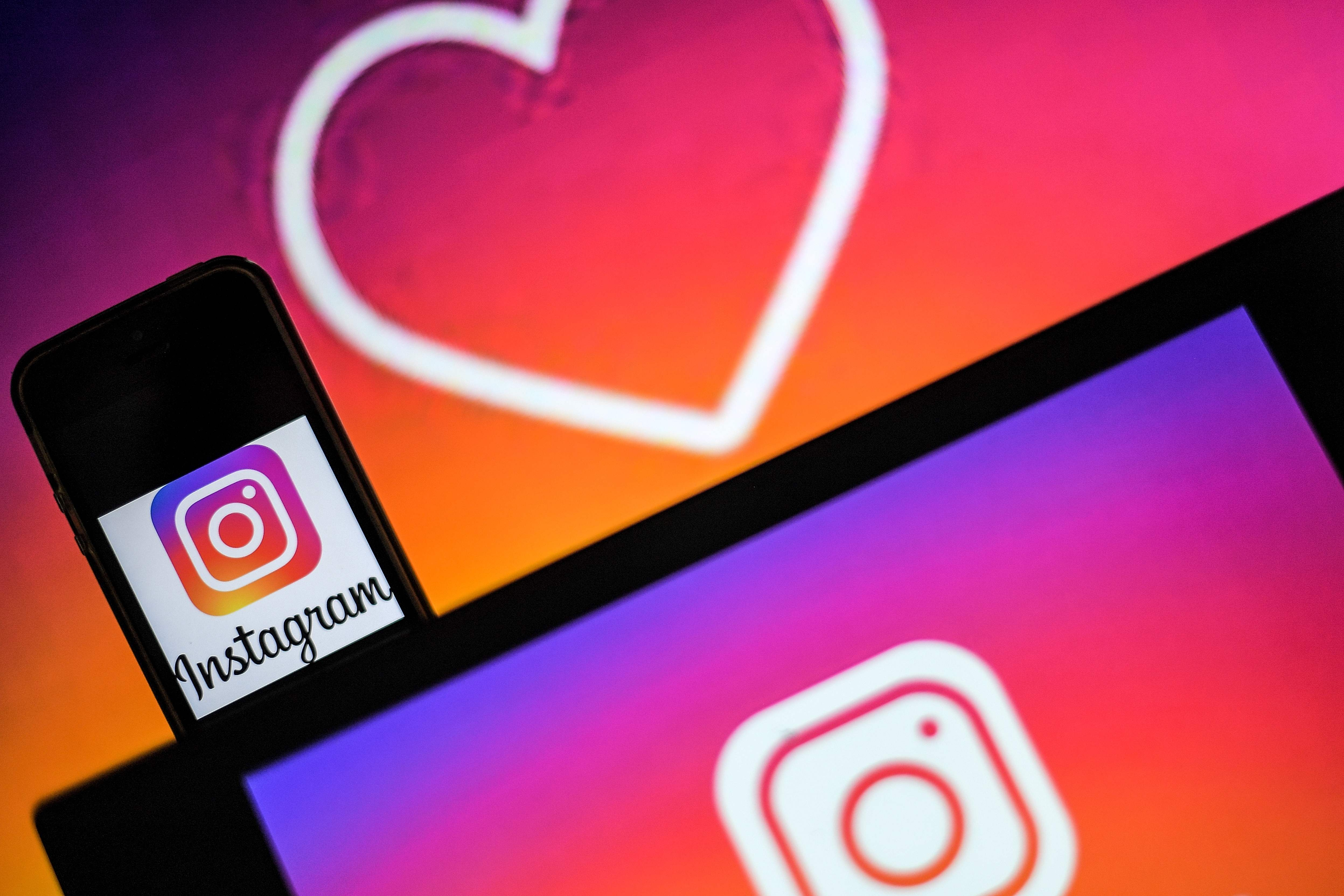 Logos of US social network Instagram are displayed on the screen of a computer and a smartphone, on May 2, 2019 in Nantes, western France. (Photo by LOIC VENANCE / AFP)