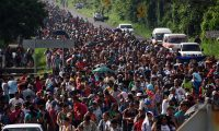 (FILES) In this file photo taken on October 21, 2018, Honduran migrants take part in a caravan heading to the US on the road linking Ciudad Hidalgo and Tapachula, Chiapas state, Mexico. - Since October 13, 2018, when the first caravan of 2,000 set off, three other similar convoys of migrants convene by social medias have left Honduras for the US in search of work or fleeing drug-traffickers. The groups are a target of President Donald Trump, who has vowed to tighten migration policy and build a wall to stop them from entering the United States through Mexico. (Photo by Johan ORDONEZ / AFP)