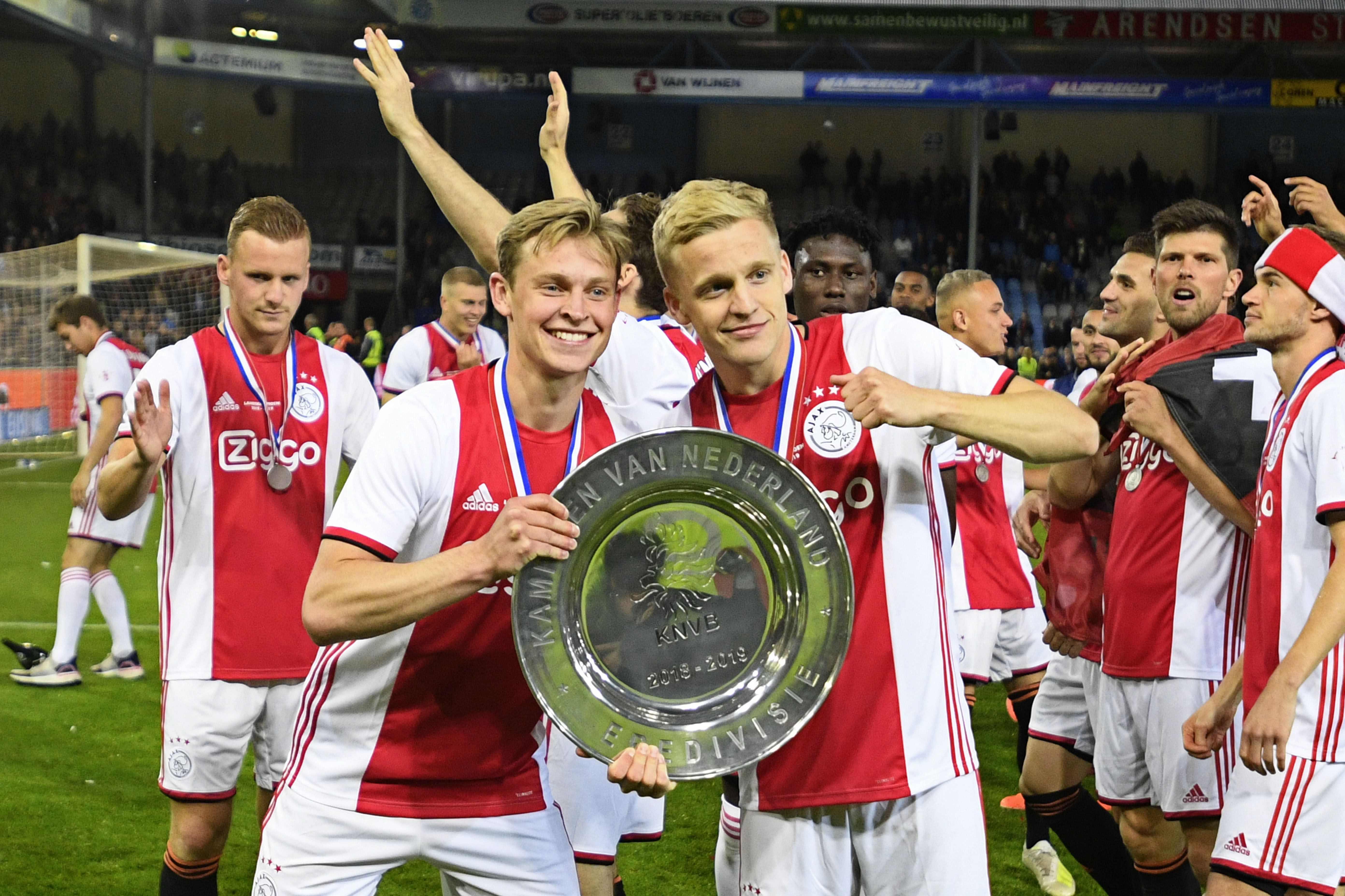 Frenkie de Jong (izquierda) celebra junto a Donny van de Beek la liga holandesa. (Foto Prensa Libre: AFP)