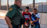"Border Patrol agent Frank Pino (L) is pictured with two migrants who presented themselves to the Border Patrol in El Paso, Texas on May 16, 2019. - ""It's heart breaking, you know, I'm a father. I have two children. These guys out here, they are here with their kids,"" Pino said, ""I kind of put myself in their position, and you know, would I do the same thing they're doing? Escaping violence or fleeing their countries, it's a hard decision, but I took an oath as a Border Patrol agent, my main priority is protecting this border, protecting this fence, and making sure that we identify for the security of my community where I live in El Paso, Texas. That's important to me."" About 1,100 migrants from Central America and other countries are crossing into the El Paso border sector each day. Pino, public information officer for the Border Patrol, says that Border Patrol resources and personel are being stretched by the ongoing migrant crisis, and that the real targets of the Border Patrol are slipping through the cracks. (Photo by Paul Ratje / AFP)"