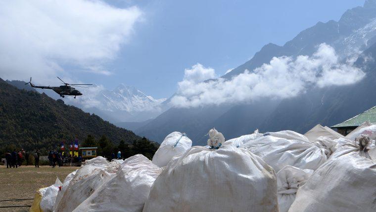 Un helicóptero del Ejército nepalí sobrevuela los desechos recolectados en el monte Everest. (Foto Prensa Libre: AFP)