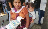 Juana Us ofrece billetes de lotería junto a su hijo Baltazar Elías, de 7 meses. (Foto Prensa Libre: Oscar Fernando García).