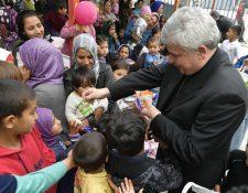 El limosnero del papa Francisco, el cardenal polaco Konrad Krajewski, reparte caramelos entre los niños durante una visita a un campamento de refugiados en las islas griegas. (Foto Prensa Libre: EFE)