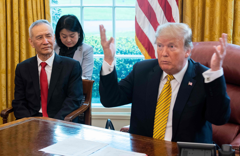 El vicepresidente de China, Liu He, junto a su par estadounidense, Donald Trump en una reunión del 4 de abril. (Foto Prensa Libre: AFP)