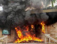 El incendio provocado por los manifestantes en la entrada a la embajada de Estados Unidos en Honduras. (Foto Prensa Libre: AFP).