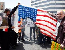 Manifestantes iraníes queman banderas estadounidenses durante una protesta contra la administración Trump. (Foto Prensa Libre: EFE)
