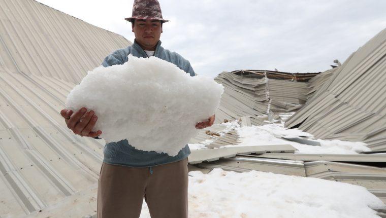 Un vecinos de Sija sostiene un bloque de hielo que se formó del granizo que derrumbó el techo de un cancha de futbol. (Foto Prensa Libre: Mynor Toc)