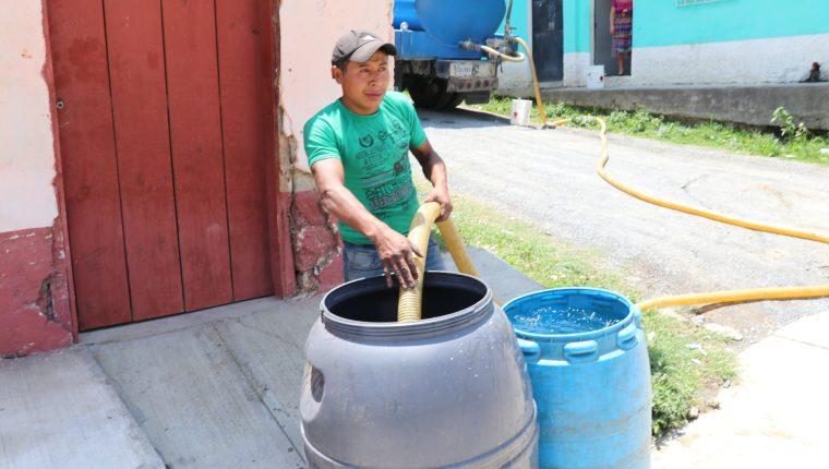 El encargado de un camión cisterna llena dos toneles de agua para un vecino de Uspantán, Quiché. (Foto Prensa Libre: Héctor Cordero).