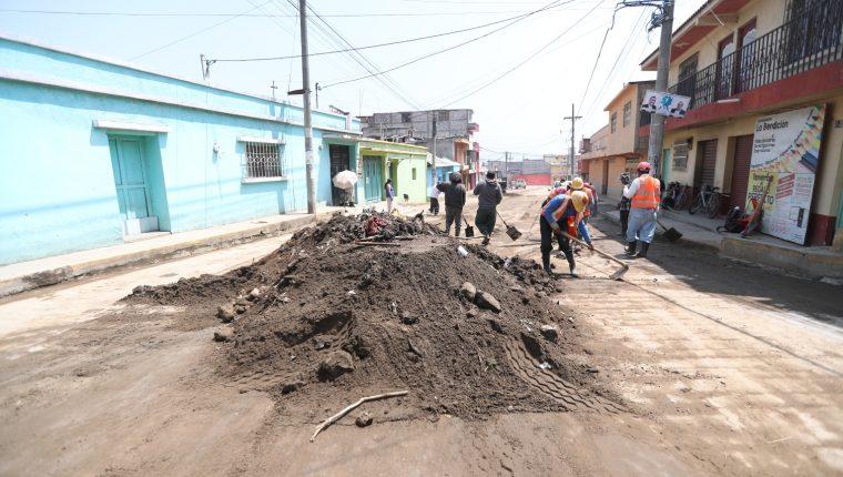 1.Vecinos y empleados municipales se unieron para recolectar el lodo y la tierra que quedó en las calles por las inundaciones. (Foto Prensa Libre:  : María José Longo)