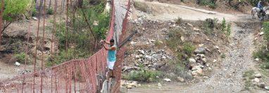 Un vecino se arriesga al cruzar el puente dañado en San Pablo, Zacapa. (Foto Prensa Libre: Mario Morales)