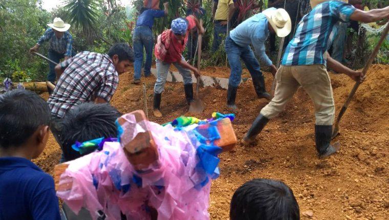 Vecinos y amigos de la familia ayudan a sepultar el féretro. La lluvia incrementó durante la sepultura. (Foto Prensa Libre: Mario Morales)
