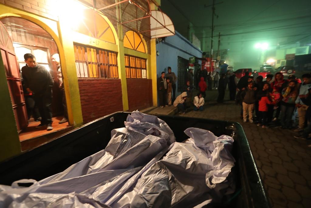 Curiosos, familiares y vecinos de la colonia San Antonio, zona 7, observan los cadáveres que serán trasladados al Inacif. (Foto Prensa Libre: Mynor Toc)