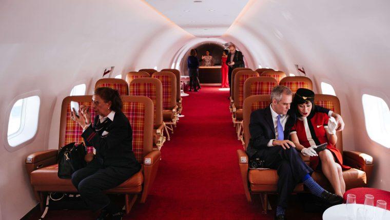 """Los visitantes se sientan en la cabina de """"Connie"""", el avión de la constelación Lockheed de 1958, restaurado como salón de cócteles en el recientemente inaugurado Hotel TWA en el aeropuerto JFK el 15 de mayo de 2019 en la ciudad de Nueva York. (Foto Prensa Libre: AFP)"""