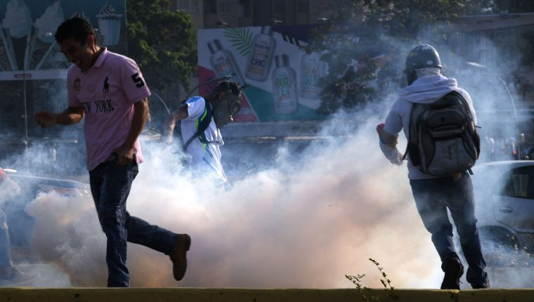 Venezuelans run away from tear gas during scuffles with security forces in Caracas on April 30, 2019. - Venezuelan opposition leader and self-proclaimed acting president  Juan Guaido said on Tuesday that troops had joined his campaign to oust President Nicolas Maduro as the government vowed to put down what it said was an attempted coup. (Photo by Yuri CORTEZ / AFP)