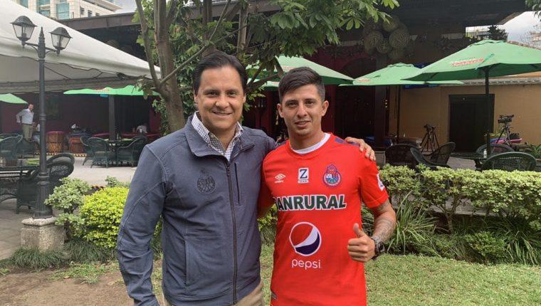 Alejandro Díaz posa con la camisola de Municipal junto al gerente de mercadeo rojo Pedro Arriaza. (Foto Prensa Libre: Twitter @Rojos_Municipal)