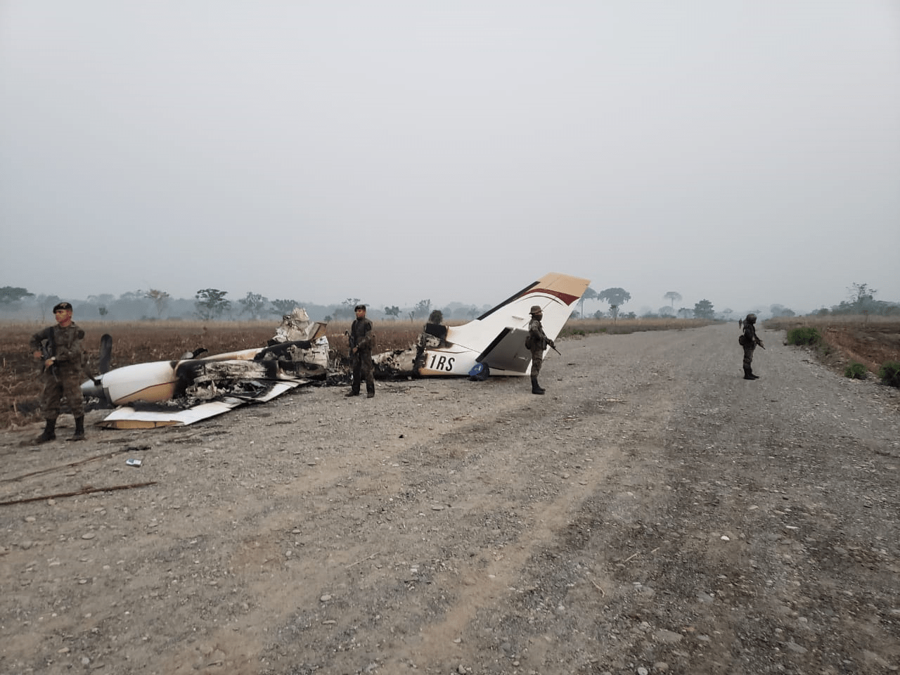 Elementos del Ejército custodian los restos de la avioneta, aunque minutos después fueron expulsados por comunitarios de la aldea Siete Cerros. (Foto Prensa Libre: Cortesía)
